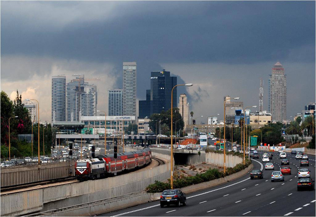 Tel Awiw, Intercity na południe złapany pomiędzy stacjami HaShalom i HaHagana. Kolej w Tel Awiwie idzie dość fotogenicznym korytarzem pomiędzy autostradą, brudną rzeczką i wieżowcami.