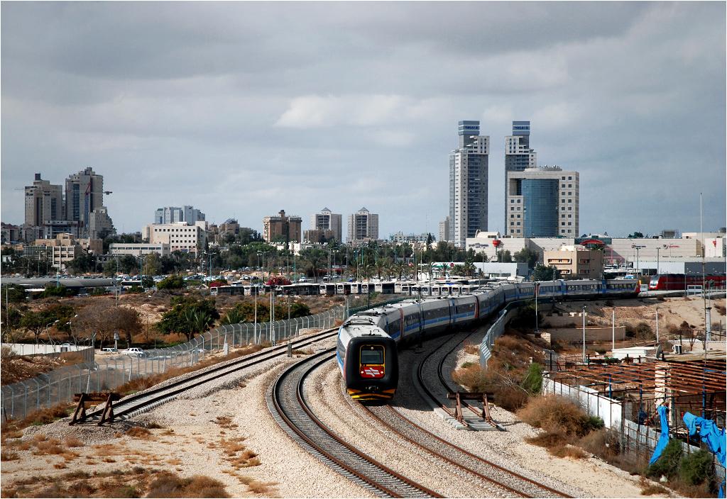 """Be'er Szewa. """"Gumowy nos"""" wyjeżdża ze stacji Be'er Szewa Centrum (Be'er Sheva Merkaz). Miasto, którego panoramę widać za pociągiem, nazywane jest """"stolicą pustyni Negew"""". Żyje tu ponad 200 tys. ludzi, choć wokół sam piasek"""