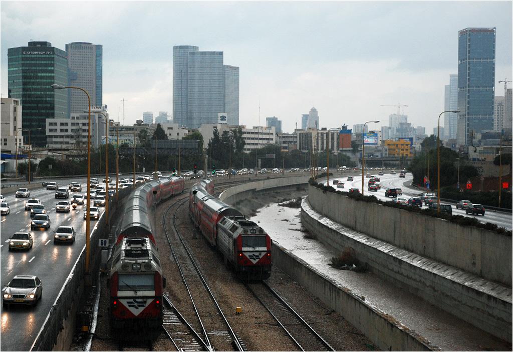 Tel Awiw. Dwa pociągi w jednym kierunku wyjechały ze stacji HaHagana i ścigają się w rzęsistym deszczu. To ostatnie składy w tym dniu, za chwilę rozpocznie się szabat