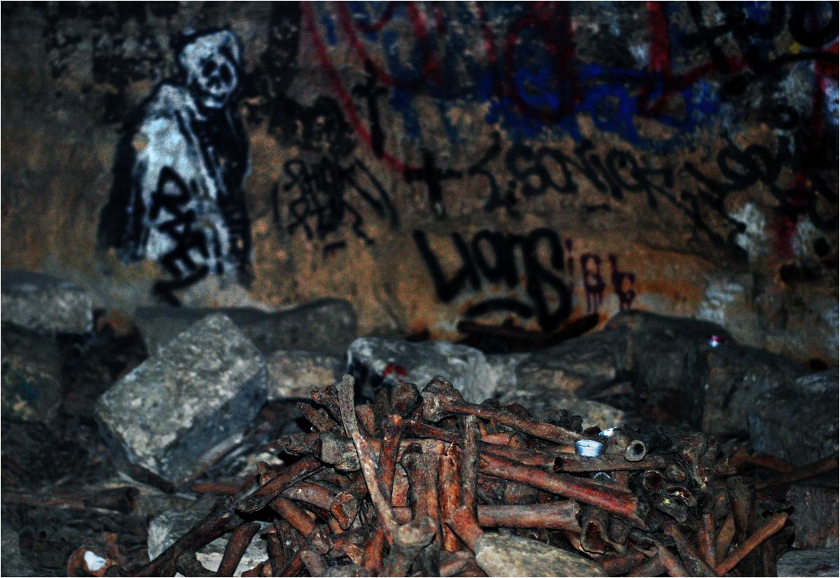 Namalowana śmierć z podziemnego Paryża spogląda na stos ludzkich kości i pozostałe na nich oznaki niedawnej imprezy