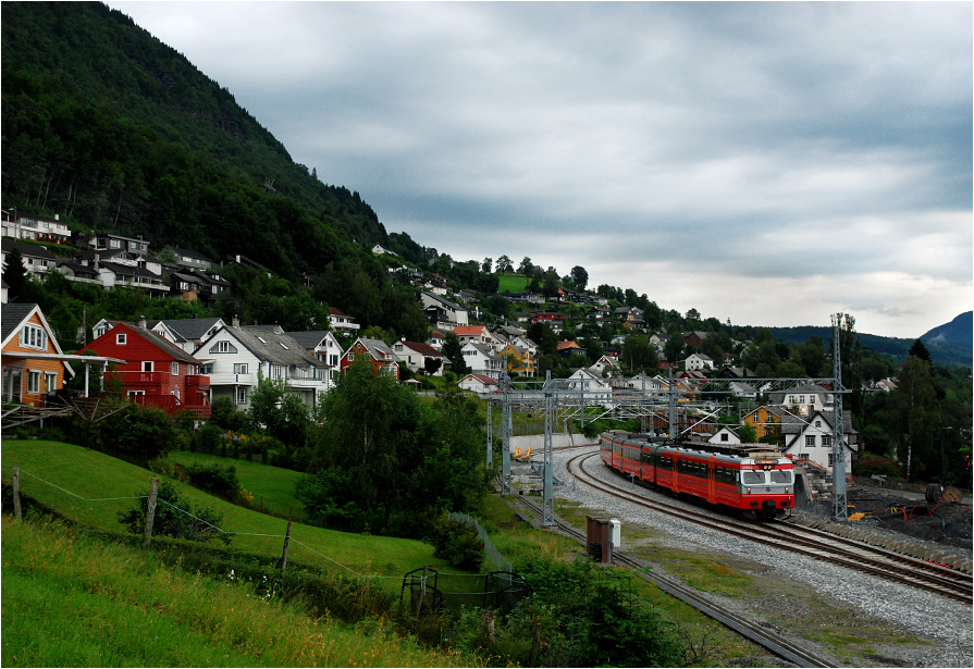 Vossevangen. Jednostka BM 69082 jako pociąg osobowy z Myrdal do Bergen opuszcza jedno z największych miast regionu Hordaland (5993 mieszkańców).