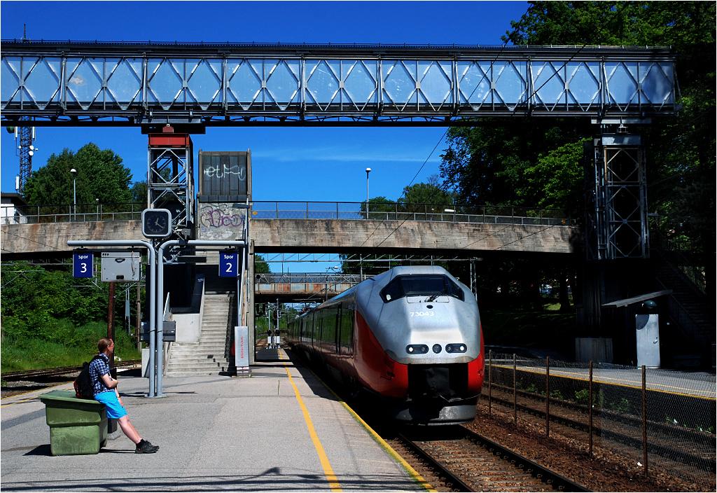 Jednostka serii 73B wjeżdża na stację w Ski jako pociąg regionalny z Oslo do Göteborga. Seria 73 może osiągnąć 210 km/h, ale nigdzie na norweskich torach jej się to nie udaje. Tylko na linii Østfoldzkiej (z Oslo na południe, do Szwecji) jeździ odmiana 73B - różniąca się między innymi malowaniem (w pozostałej części Norwegii dół serii 73 jest niebieski).