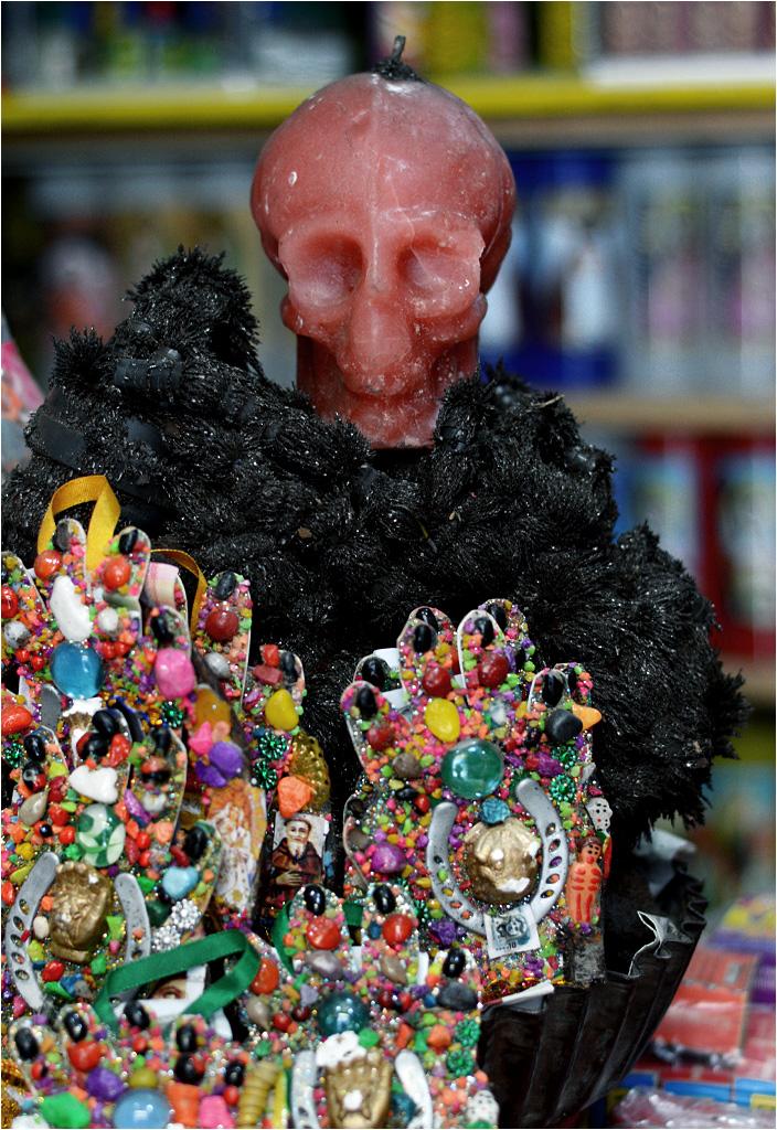 Woskowa czaszka sąsiaduje z wizerunkami katolickich świętych