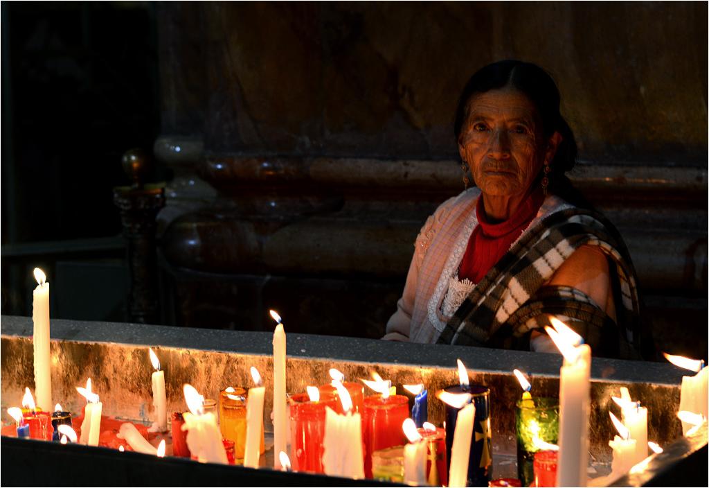 Cuenca, Ekwador. Kobieta pali świecę podczas adwentowej modlitwy
