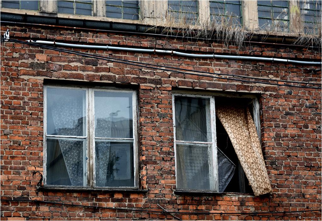 W niektórych oknach powiewają kremowo-brązowe zasłony PKP, dobrze znane z przedziałów pociągów pospiesznych
