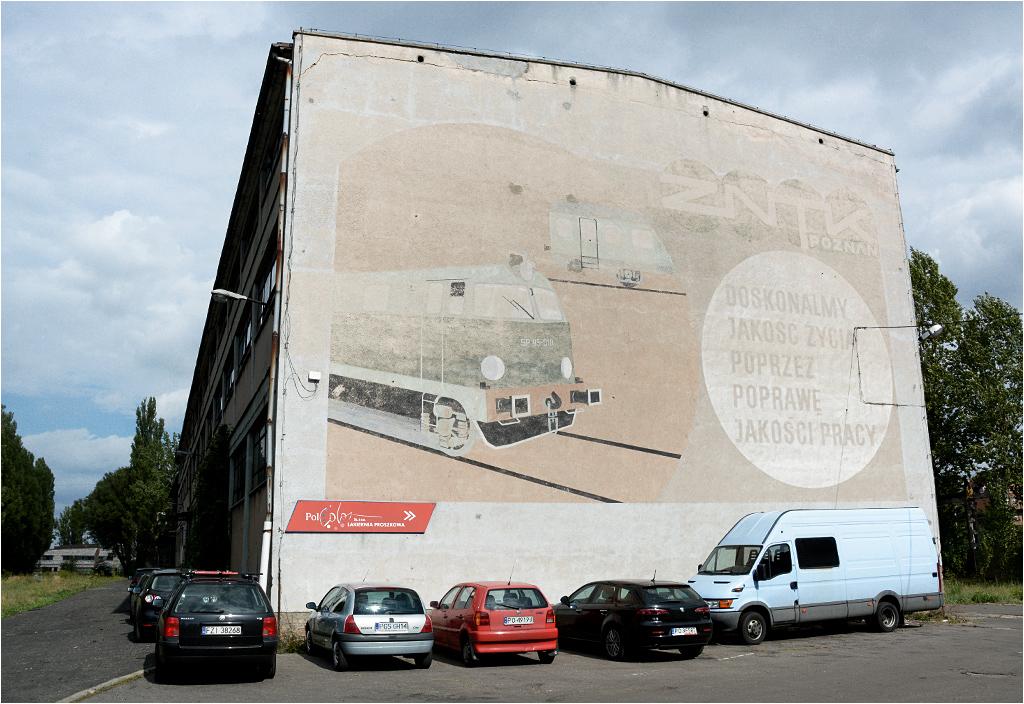 Wyblakły mural z lokomotywą SP45-010 przypomina o dawnym przeznaczeniu zakładu. Dzisiaj w niektórych budynkach mieszczą się zewnętrzne firmy, którym ZNTK wynajmuje powierzchnię biurową