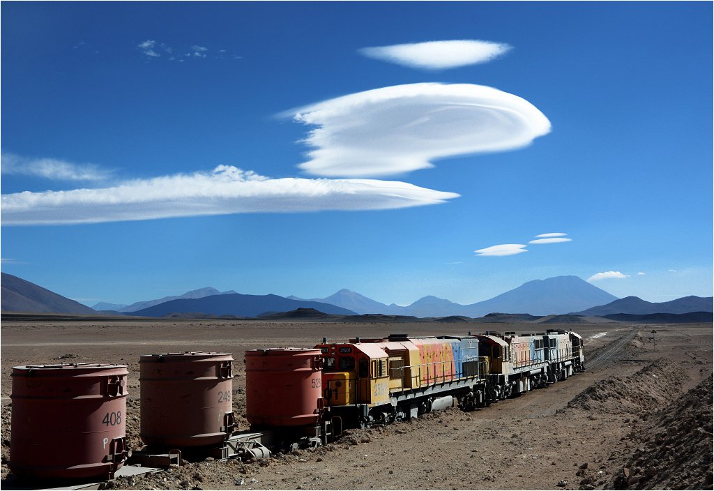 Chile - trio ciężkich wąskotorowych (1000 mm) lokomotyw GL26C zmierza nad ocean z transportem rudy cynku. Wokół rozciąga się jedno z najsuchszych środowisk na świecie - pustynia Atakama