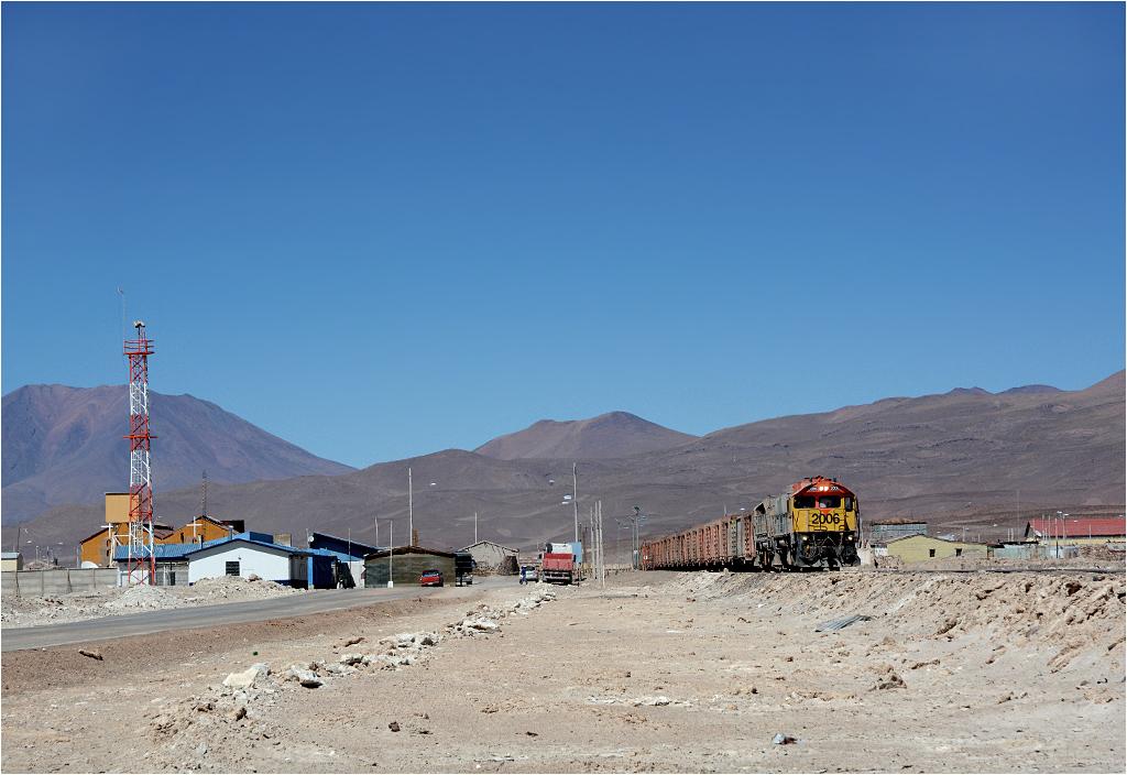 Ollagüe-Avaroa. Duet lokomotyw GL26C przekracza granicę z Boliwią (białe budynki po lewej stronie to zabudowania przejścia granicznego)