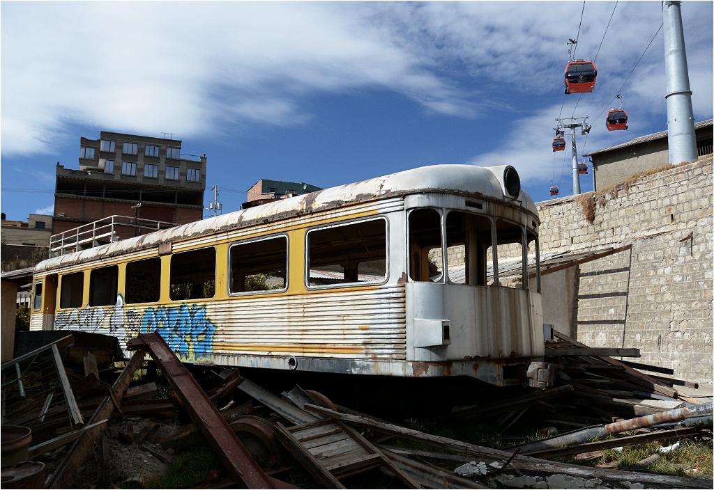 Ryflowany wagon motorowy, niegdyś obsługujący linię do Guaqui, dogorywa za nieczynną już stacją w La Paz. Nad nim biegnie trasa nowej kolejki gondolowej