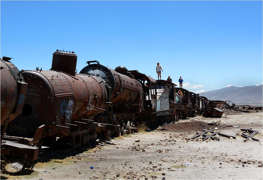 Turyści spacerują po parowozach pozostawionych na cmentarzysku lokomotyw w Uyuni
