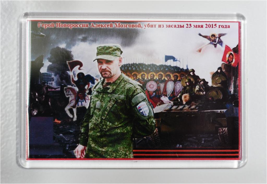 """""""Bohater Noworosji Aleksiej Mozgowoj, zabity w zamachu 23 maja 2015 roku"""". Warto dokładniej przyjrzeć się magnesowi i zwrócić uwagę na detale. Tam dzieje się WSZYSTKO. Jest wojsko, anioły, twarz Chrystusa, wybuchy..."""