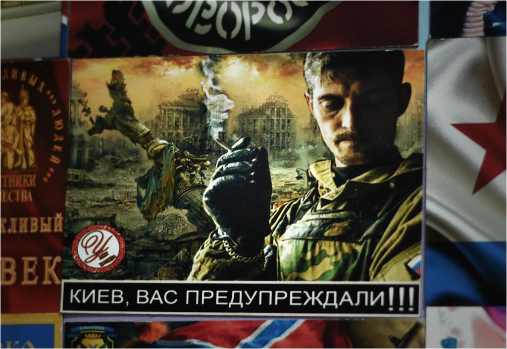 """Napis głosi """"Kijów - ostrzegaliśmy!!!"""". W tle widać zniszczone budynki na kijowskim Placu Niepodległości (Majdanie). Człowiek z papierosem to Giwi, jeden z bardziej znanych bojowników Noworosji"""