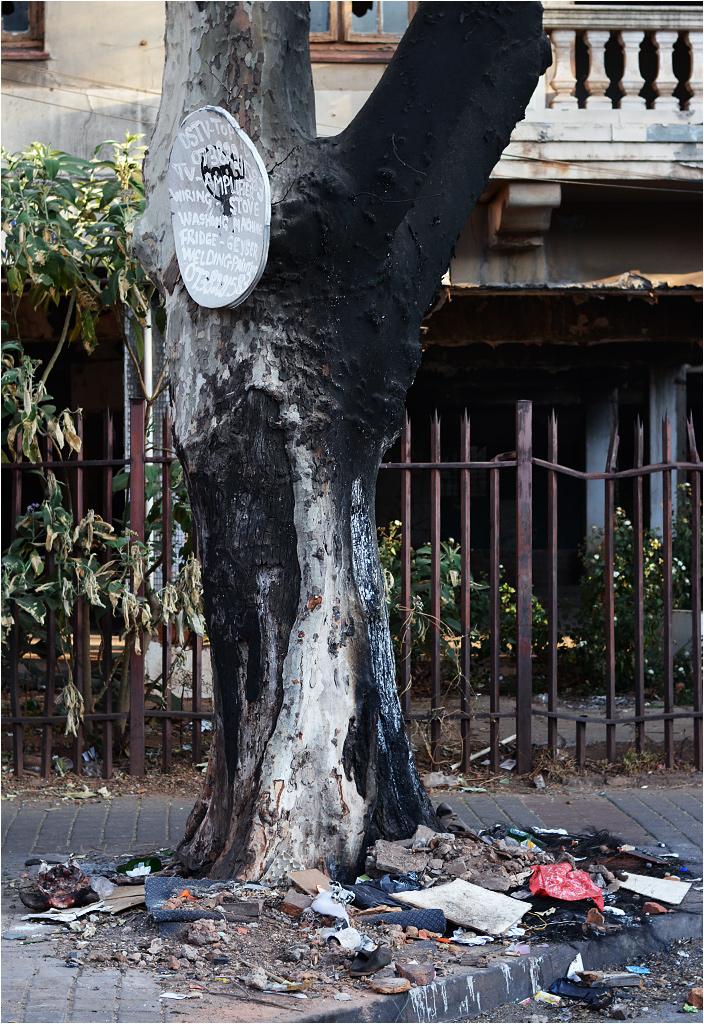 Hunter Street w dzielnicy Yeoville. Na pierwszym planie widać nadpalone drzewo, pod nim - stertę śmieci. W tle widnieje jeden z opuszczonych (przejętych?) budynków. Stara antena satelitarna służy jako nośnik reklamowy
