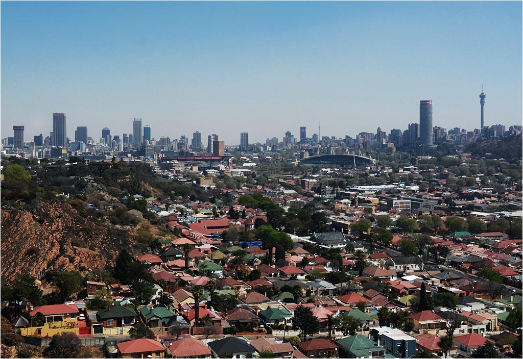 Przedpołudniowy widok na Johannesburg. Na pierwszym planie lepsze dzielnice klasy średniej, w tle getto zwane centrum miasta (lewa strona) oraz dzielnica Hillbrow (prawa strona). Widoczna przy prawej krawędzi wieża obserwacyjna od wielu lat jest zamknięta na głucho