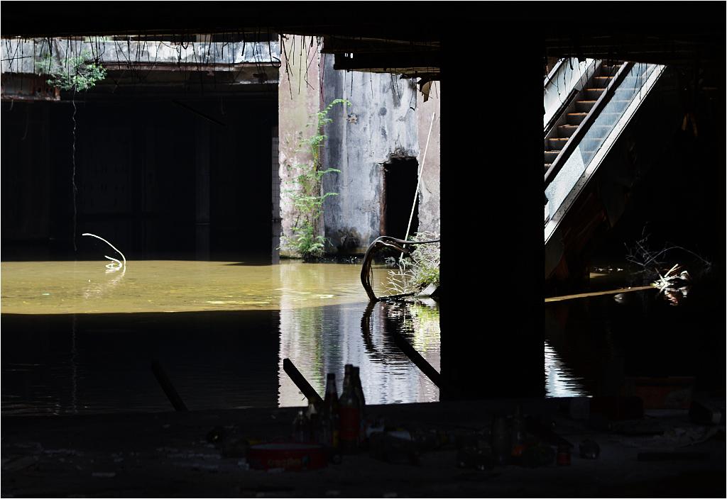 Opuszczona galeria handlowa w centrum Bangkoku. Widok przez szparę w elewacji