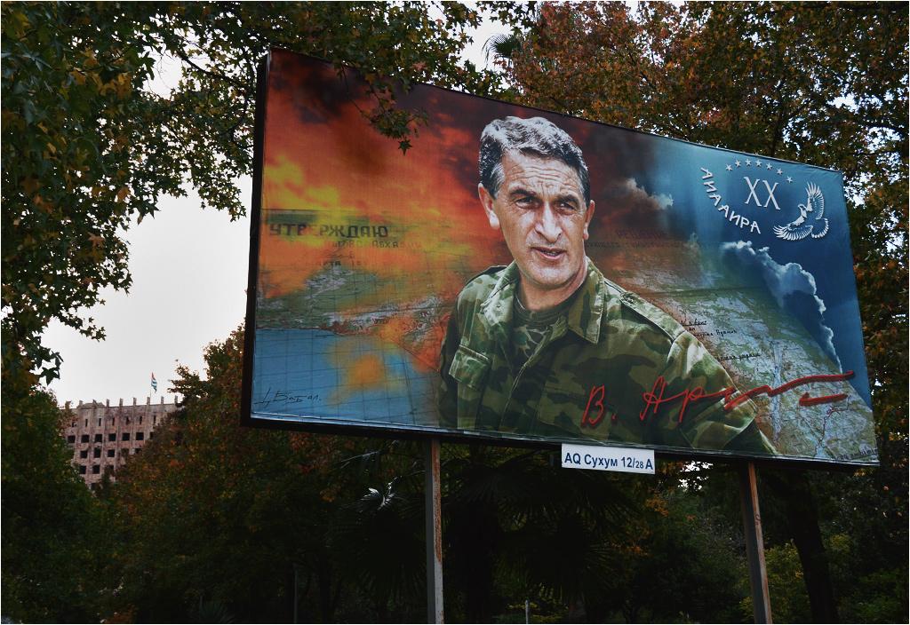 """""""Ajaaira!"""" obwieszcza Władysław Ardzinba z plakatu stojącego przed abchaskim parlamentem"""