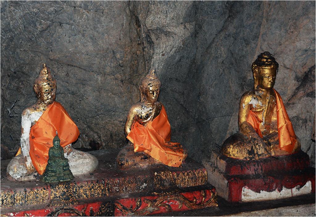 Pod ścianami jaskini stoją pozłacane i ubrane w pomarańczowe szaty posągi