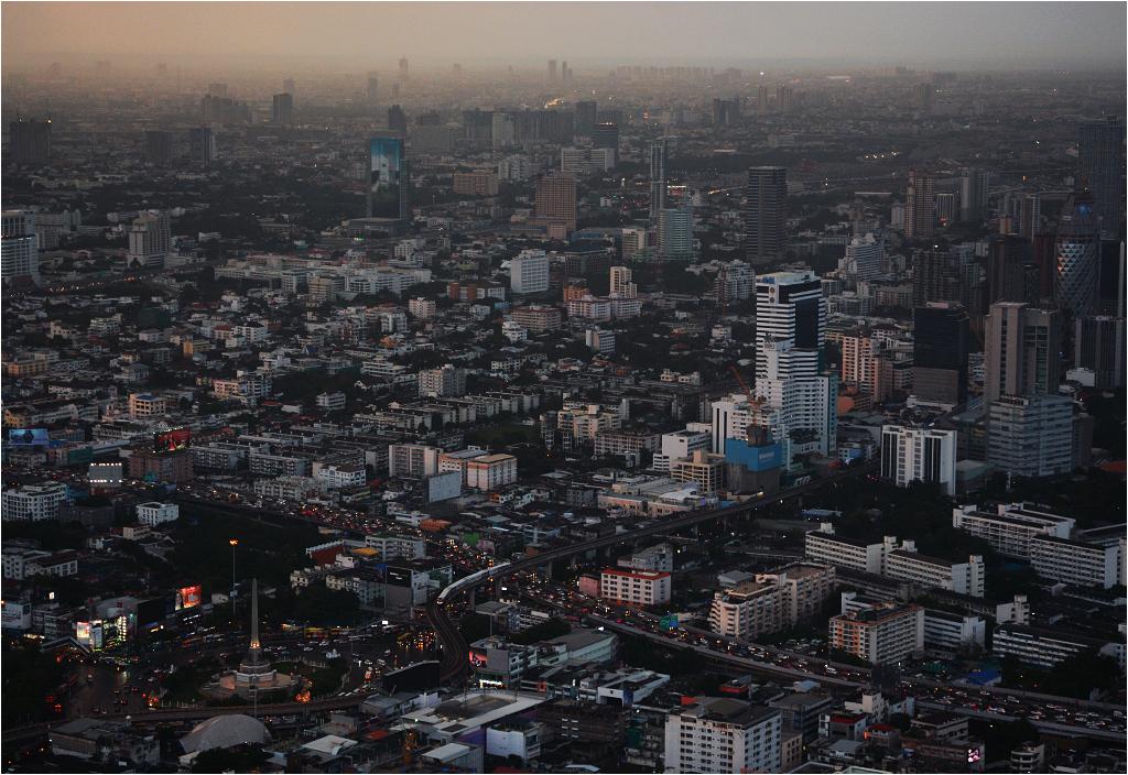 Bangkok o zachodzie słońca. Pociąg SkyTrain zbliża się do stacji National Monument