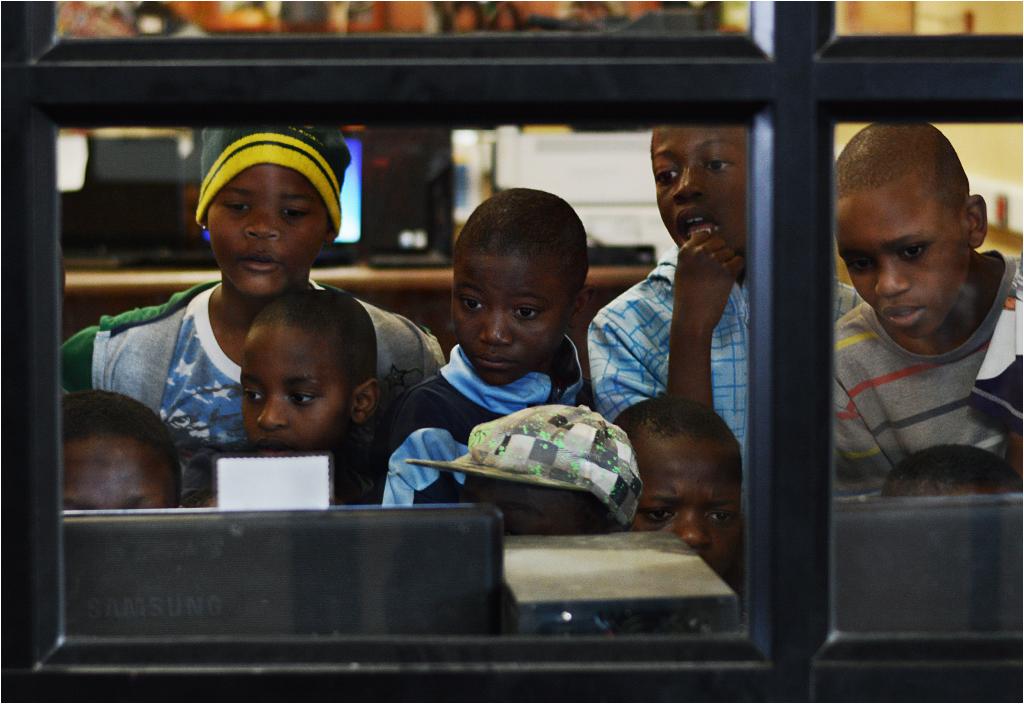 Dzieciaki z Ponte są tak zaaferowane grą komputerową, że nie zauważają stojącego za szybą fotografa