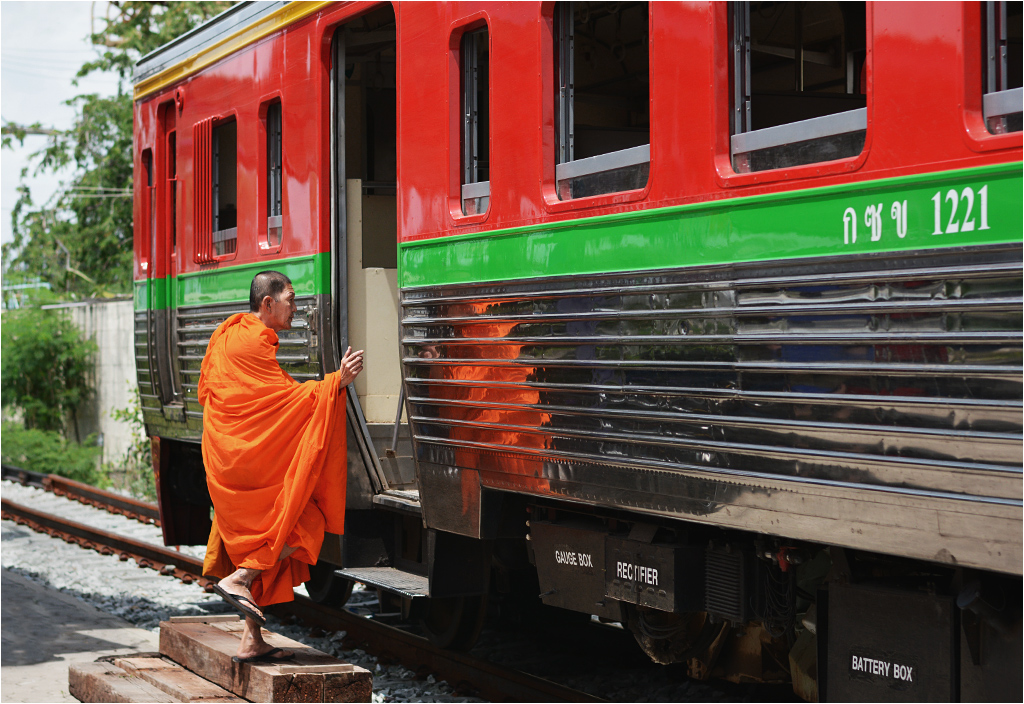 Ban Laem. Buddyjski mnich wsiada do pociągu zmierzającego w stronę Mae Klong