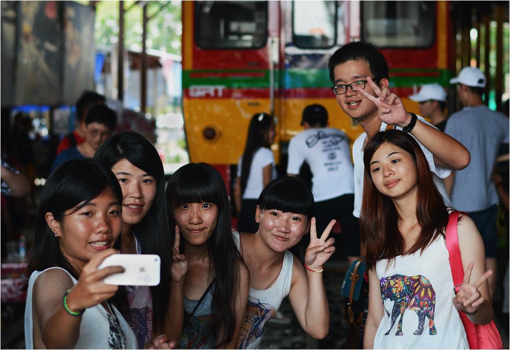 Grupa młodych Japończyków robi sobie zdjęcie na tle pociągu