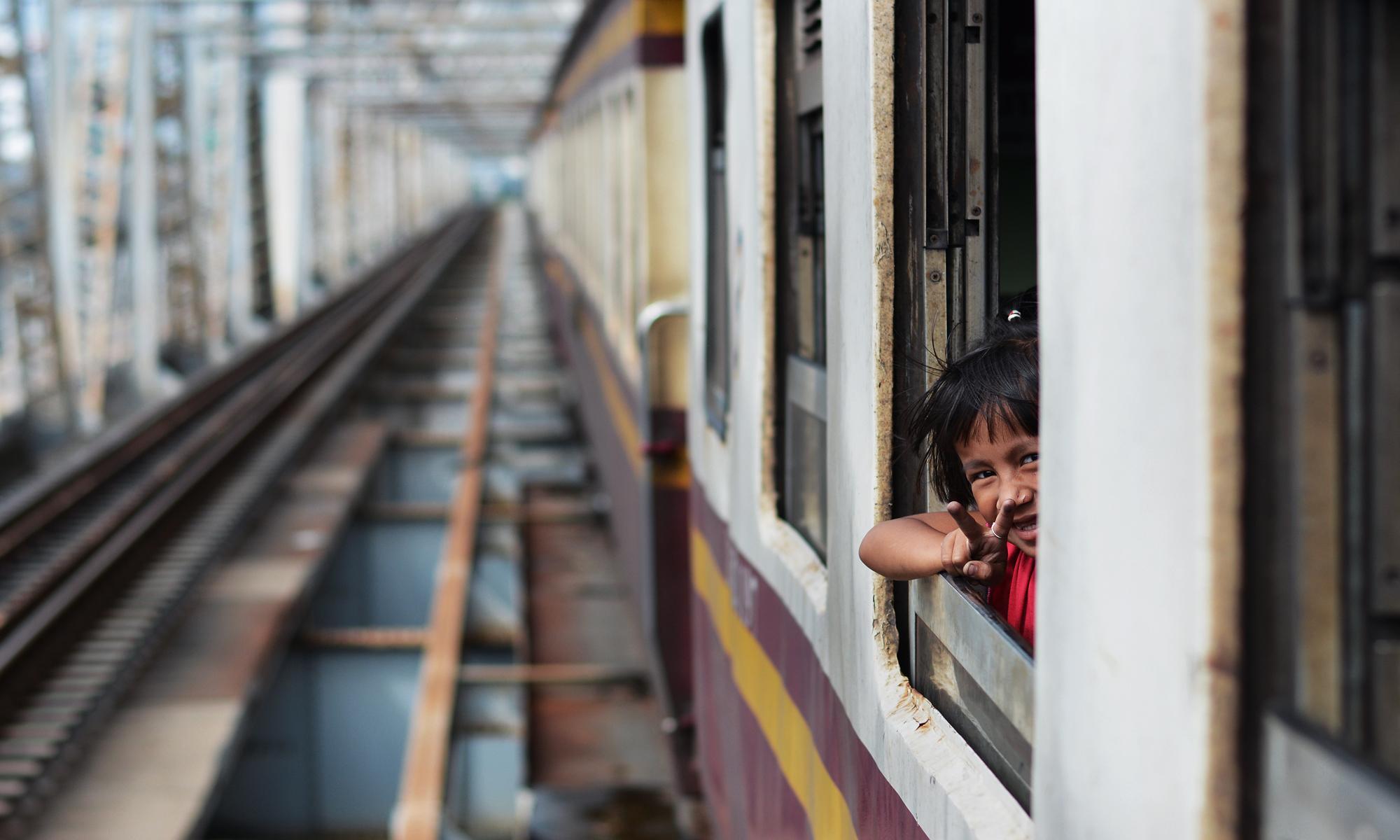 Mała dziewczynka wygląda przez okno pociągu podczas przejazdu przez most imienia króla Ramy VI w Bangkoku
