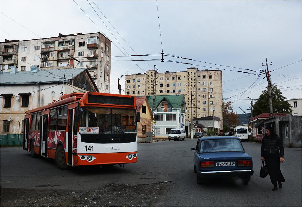 Suchumi, ulica Nazadze. Pasażerka wysiadła z samochodu i pędzi do stojącego na pętli trolejbusu