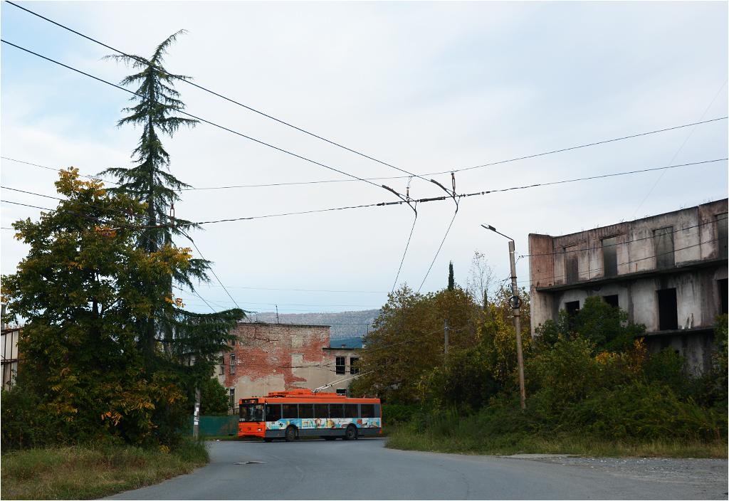 Suchumski trolejbus przejeżdża obok typowych dla miasta opuszczonych budynków