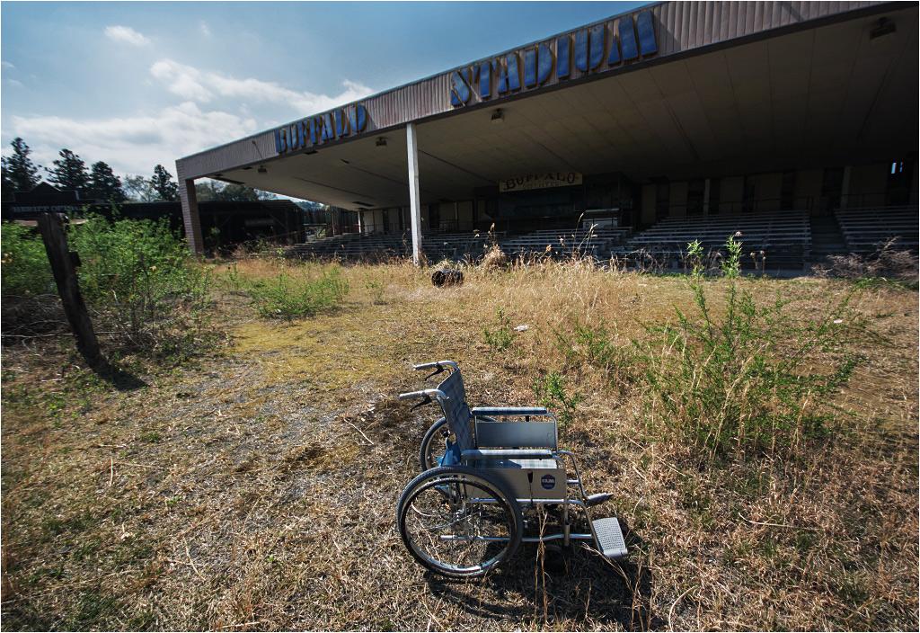 """Przed bizonim stadionem stoi stary wózek inwalidzki. Punkt obowiązkowy. +10 do ogólnej kripiości miejsca (""""kripiość"""" - polski rzeczownik od angielskiego przymiotnika """"creepy"""")"""