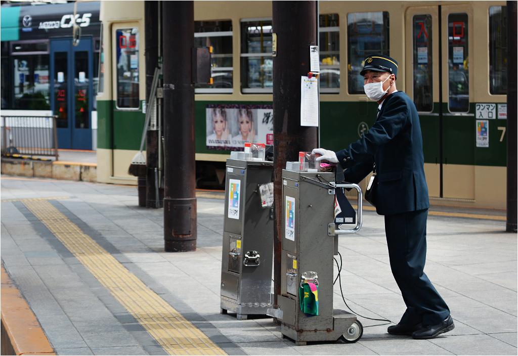 Kontroler pobiera opłatę na przystanku pod dworcem kolejowym w Hiroszimie