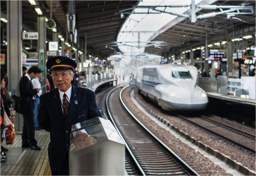 Nagoja, perony szybkiej kolei. Widoczny na zdjęciu pracownik kolei jest kimś pomiędzy zawiadowcą, peronowym dyżurnym ruchu, a sokistą - stoi na peronie i pilnuje, żeby nikt nie zbliżał się do jego krawędzi. W razie awaryjnych sytuacji dysponuje systemem nagłaśniającym, z pomocą którego upomina niesubordynowanych podróżnych