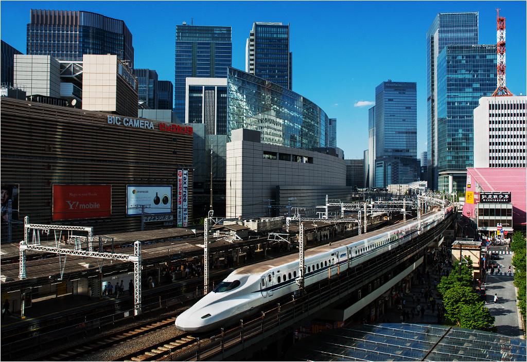 Tokio. Szesnastowagonowy Shinkansen serii 700 jako pociąg Nozomi z Tokio do Osaki lub Hakaty wyruszył przed chwilą ze stacji początkowej. Po lewej widać perony obsługiwanej przez kolej podmiejską stacji Yurakucho