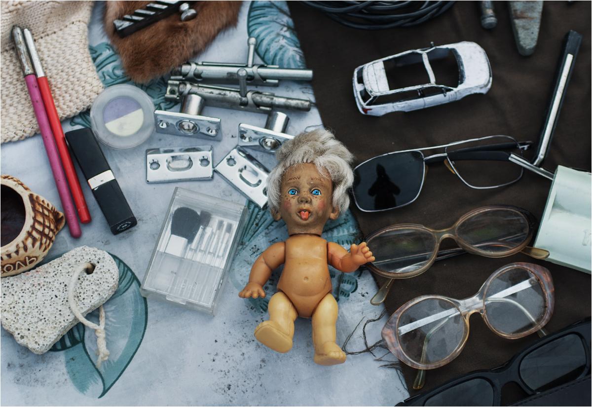 Pojemnik na sól, wrak zabawkowego samochodu, zestaw starych okularów i lalka, wyglądająca trochę jak parodia Donalda Trumpa