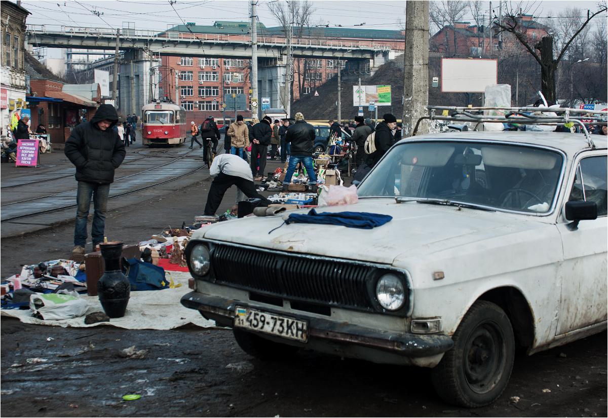 Właściciel tej starej Wołgi prowadzi sprzedaż bezpośrednio z bagażnika. W tle pomykają tramwaje - to Kijów