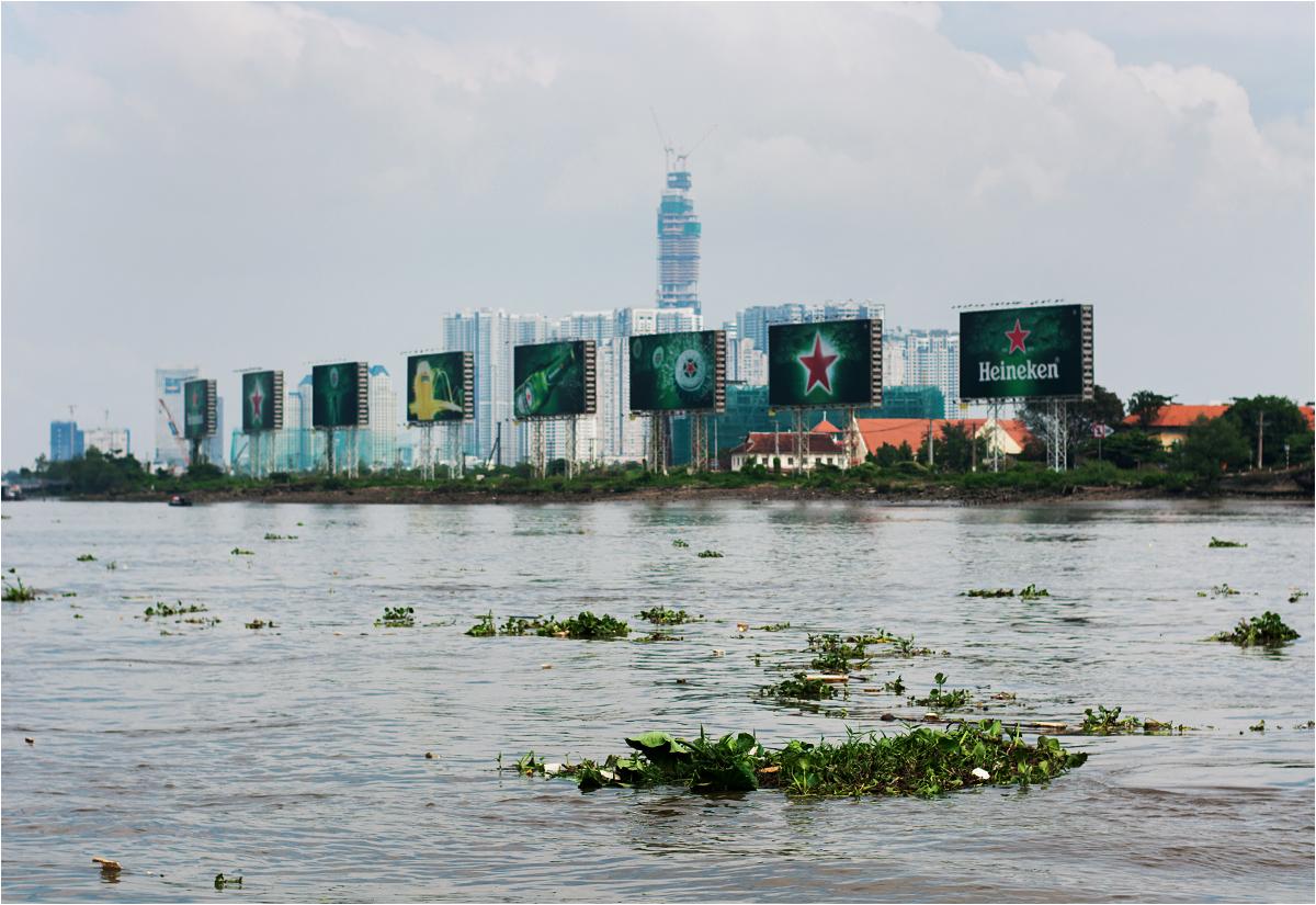Odpadki płynące Saigon River. Co chwilę przepływa nowa kępa śmieci, wymieszanych z rzecznym zielskiem