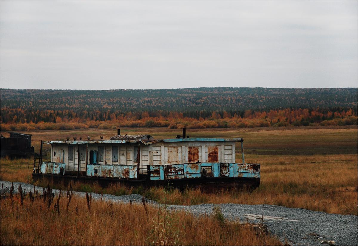 Opuszczony statek stoi na nadrzecznej nizinie w Mużach