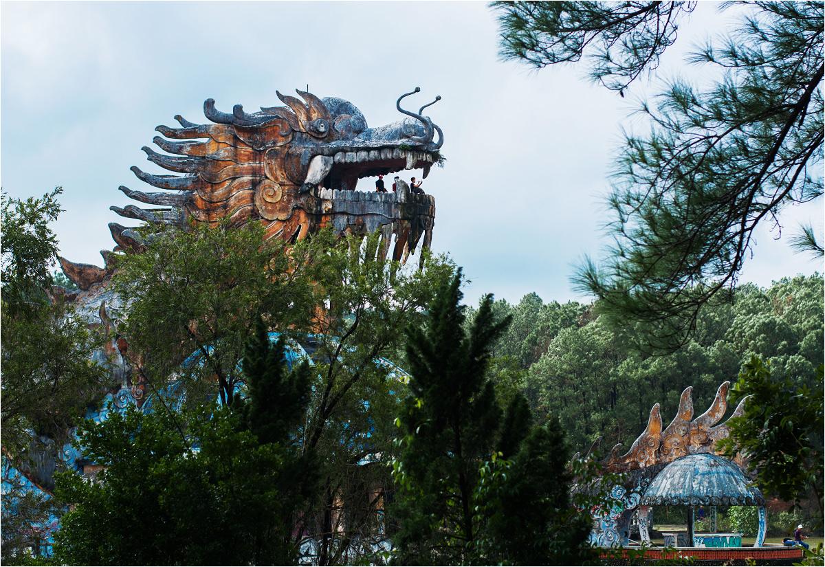 Wielki smok z turystami w paszczy wyłania się zza drzew
