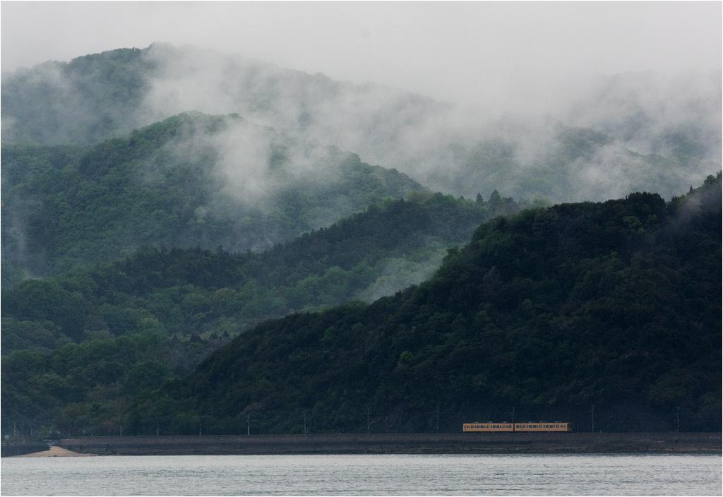 Oniryczny krajobraz japońskiego wybrzeża. Pociąg osobowy do Mihary przeciska się pomiędzy morzem a górami