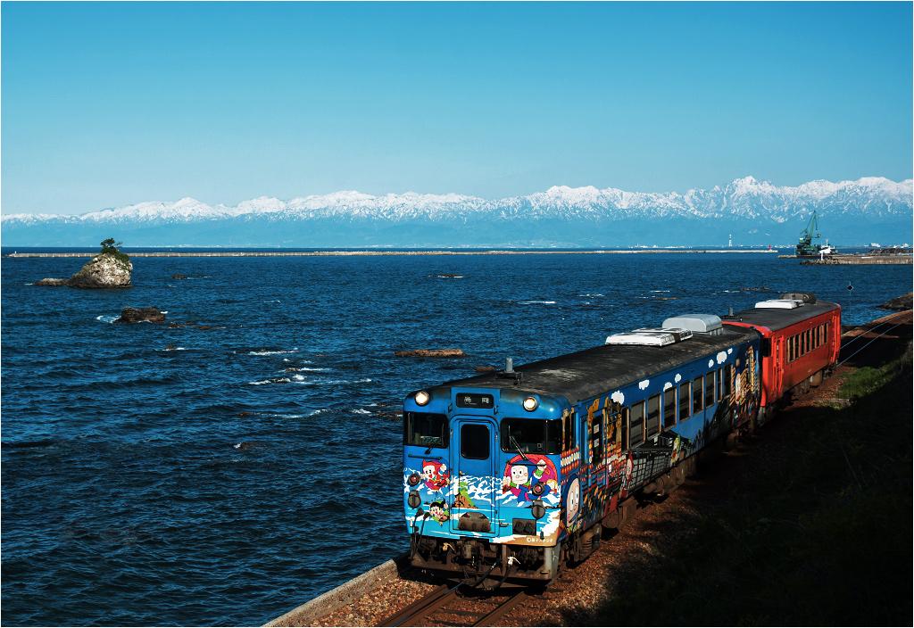Linia Himi. Za oknami pociągu faluje Morze Japońskie, a z tyłu widać łańcuch Alp Japońskich. Pierwszy wagon pomalowany jest w schemat kultowego komiksu Ninja Hattori