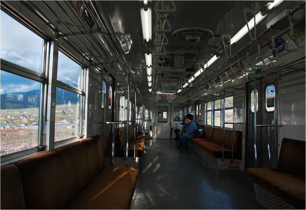 Typowe wnętrze japońskiego pociągu osobowego. Większość lokalnych składów jest wyposażona w siedzenia ustawione bokiem do kierunku jazdy