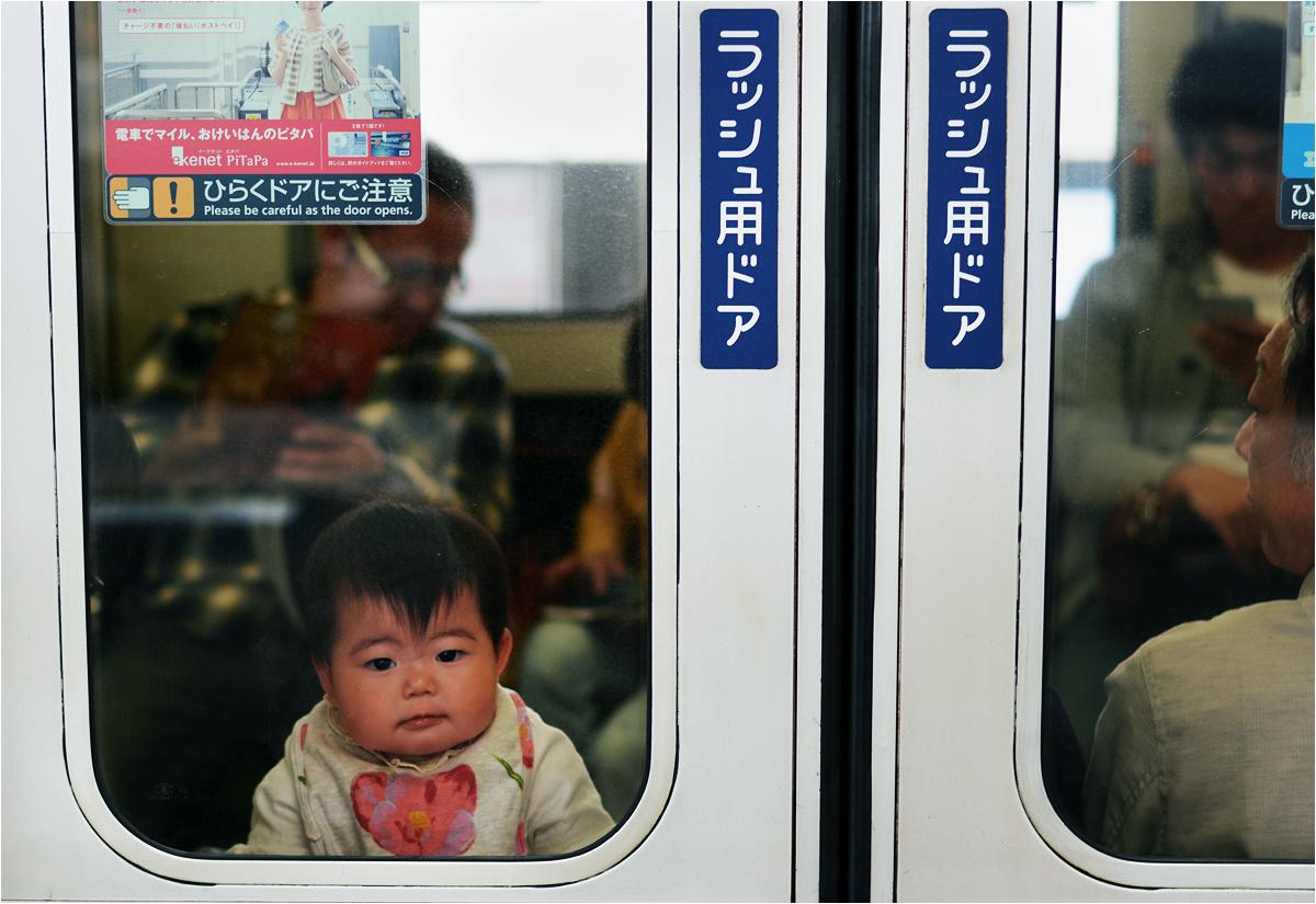 Młody pasażer jednego z pociągów aglomeracyjnych w Kioto obserwuje interesujący go świat