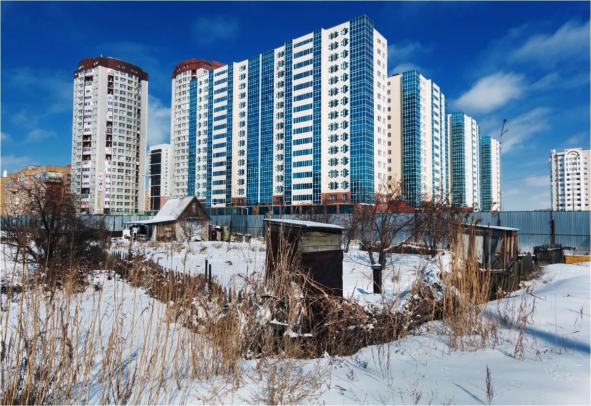 Tuż za kompleksem apartamentowców w centrum miasta wyrastają drewniane sławojki