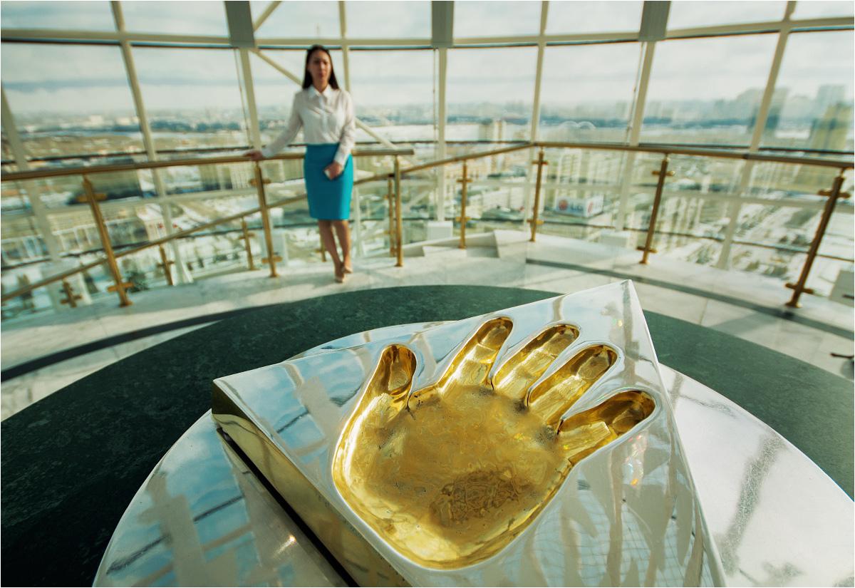 Złota dłoń prezydenta Nursułtana Nazarbajewa w wieży Bajterek. W tle hostessa, której ubiór dopełnia narodowe barwy Kazachstanu (turkus i złoto)