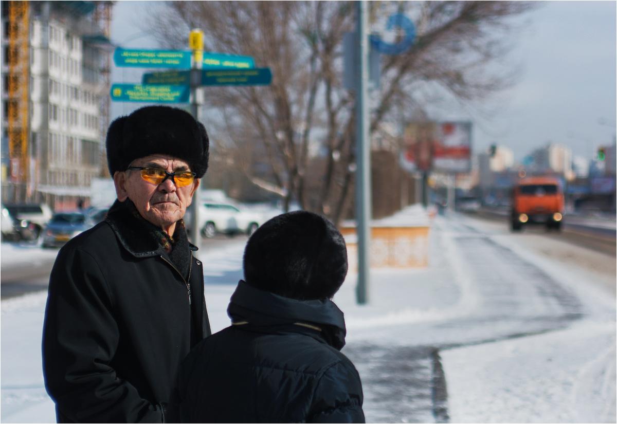 Emeryci w czapkach uszankach czekają na autobus. Klimat nie rozpieszcza Astany - to najdalej na północ wysunięta stolica Azji; położenie w środku kontynentu czyni ją też jednym z bardziej oddalonych od mórz miast świata. Zimą nadchodzą tęgie mrozy, a latem - nieznośny skwar