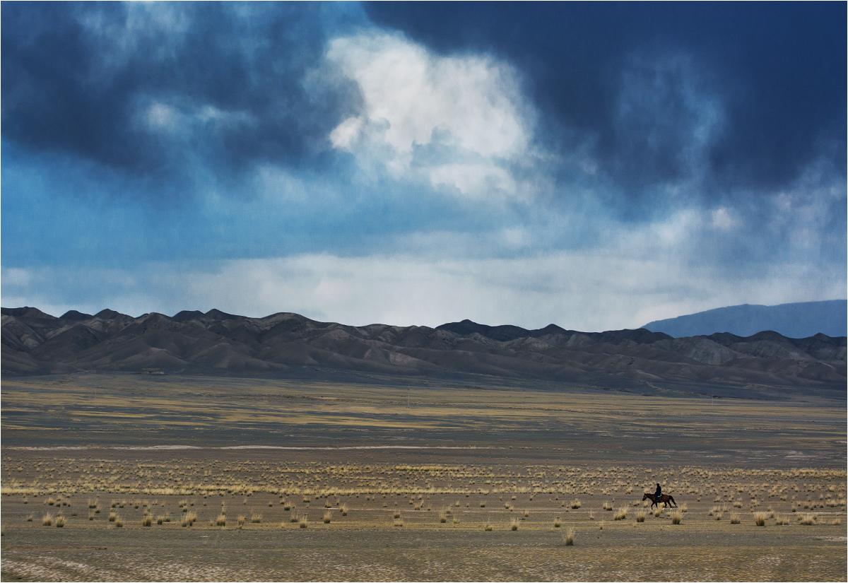 Kirgiskie widoki podróżne. Samotny jeździec przemierza step - zdjęcie zostało zrobione przez otwarte okno pędzącego samochodu
