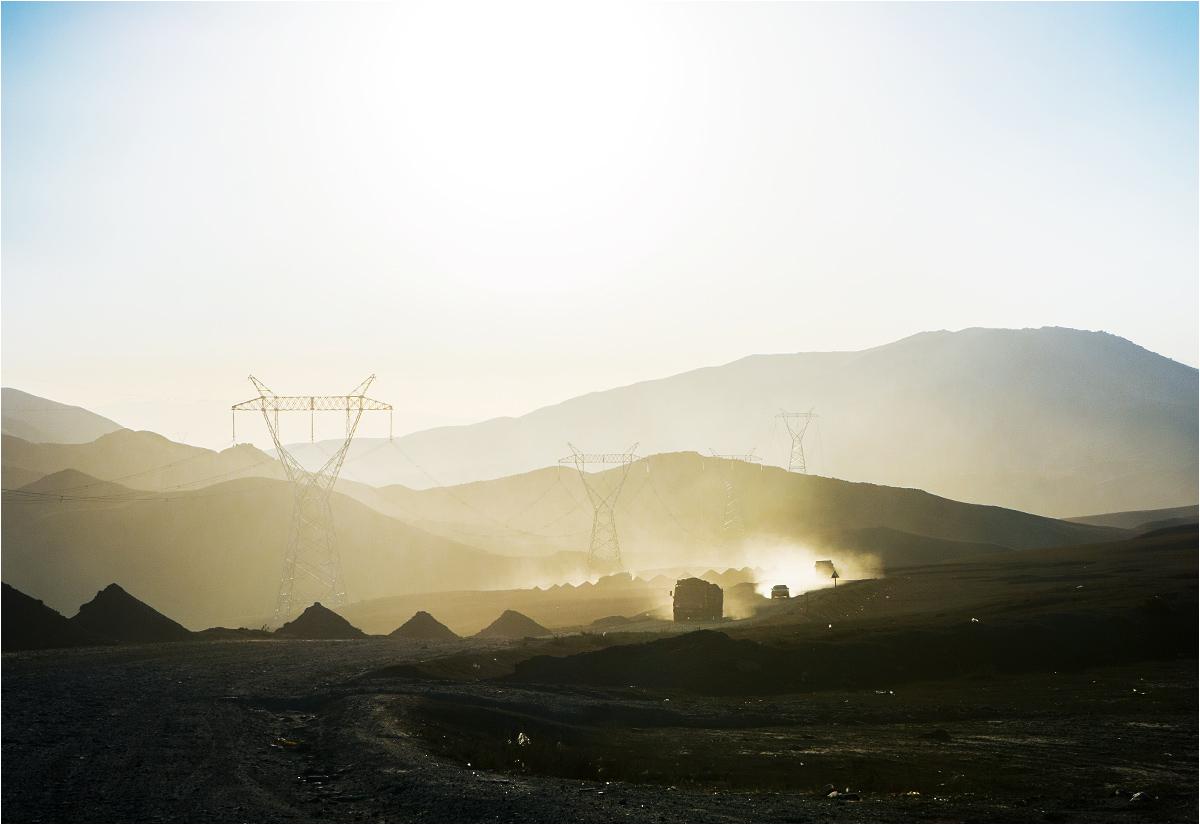 Kirgiski pejzaż autostopowy. Ciężarówki wzbijają tumany pyłu, jadąc po piaszczystej drodze