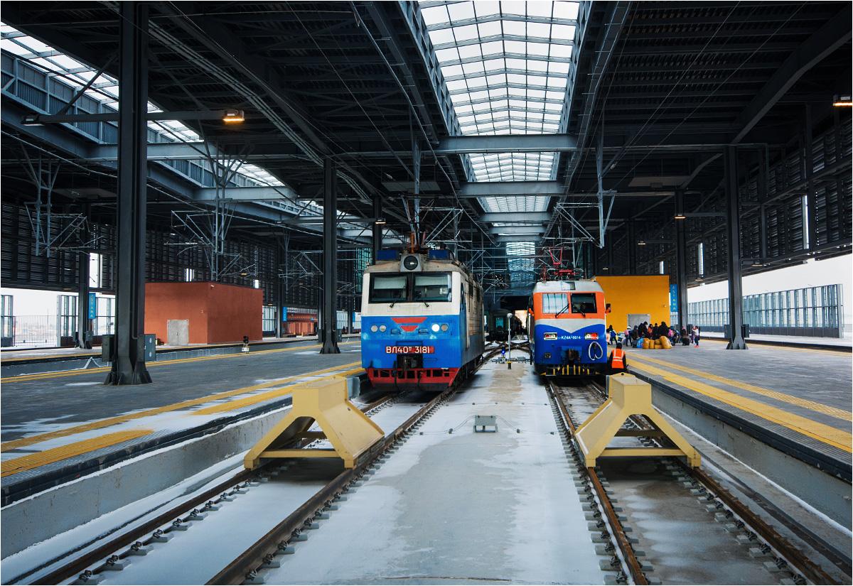 Dwa elektrowozy odpoczywają przy końcu peronu dworca Astana Nurły Żoł
