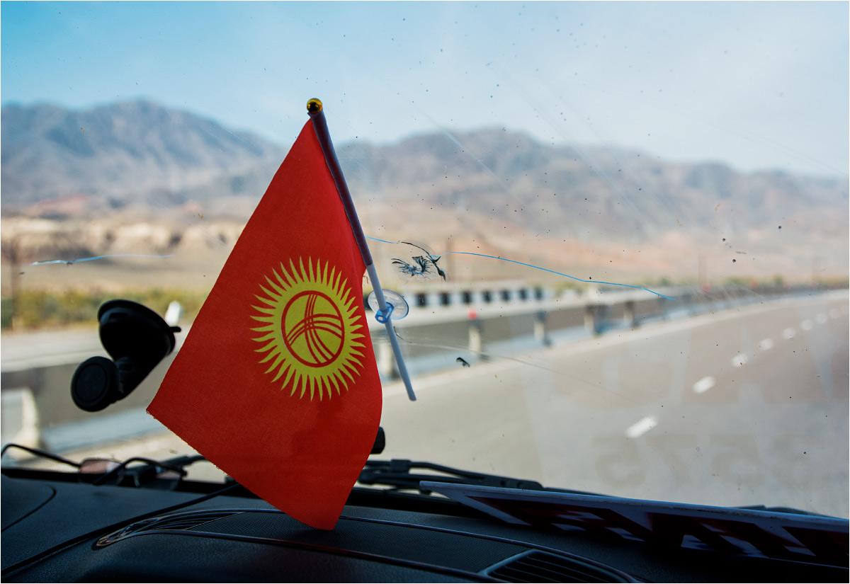 I jego flaga na tle kirgiskiego pejzażu drogowego