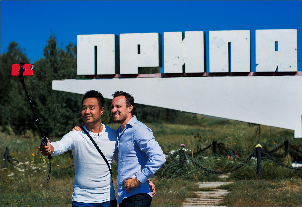 Turyści robią sobie selfie przed słynnym znakiem wjazdowym do Prypeci