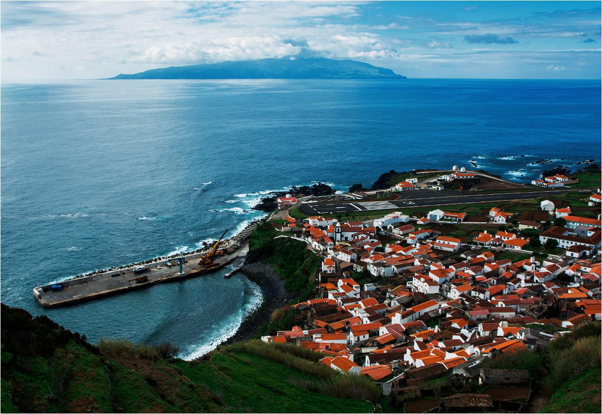 Widok z góry na Vila do Corvo. Widać lotnisko, niewielki port, kościół. W tle wyłania się wyspa Flores